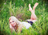 Cheerful lovely young woman lying among green grass and flowers