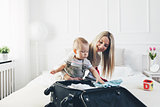 Travelling with kids. Happy mother with her child packing clothes for holiday