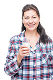 Portrait of a brunette in pajamas with a glass of milk isolated