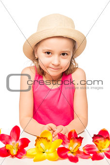 little girl and a bunch of exotic flowers on a table on a white