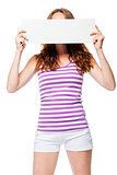 Red-haired girl hides her face behind the poster