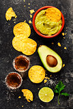 Bowl of mexican nachos chips with homemade fresh guacomole sauce