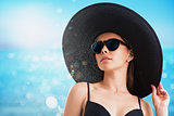 Girl with hat and sunglasses at the beach