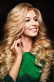 Portrait of elegant sexy blonde woman with long curly hair and glamour makeup.