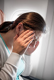 A woman with a migraine near a window in an airplane
