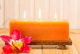 big burning candle and tropical flower on a wooden table