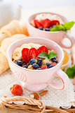 Porridge with banana and fresh berries in a cups.