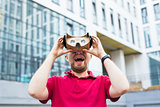 Funny man using cardboard virtual reality goggle outdoors