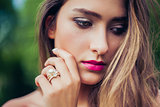 Portrait of beautiful girl with professional makeup. Stacking rings jewelry