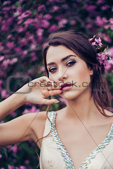 Portrait of young beautiful woman posing among spring blossom trees.