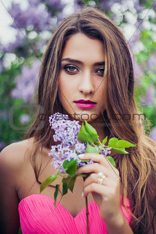 Portrait of young beautiful woman holding a lilac branch