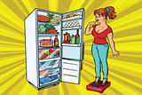 Diet. Young woman on scales, stand next to the refrigerator with