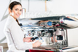 Young waitress using an automatic coffee machine