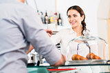 Beautiful waitress serving male customer with a cup of coffee fo