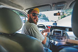 funny smiling bearding man with glass of vine in the car