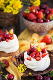 Delicious mini Pavlova meringue cake decorated with fresh berrie
