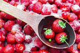 Against a background of strawberries with sugar a wooden spoon for jam.