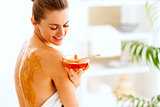 Happy young woman sitting on massage table with honey plate