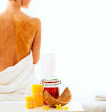 Closeup on honey spa therapy ingredients and relaxed young woman