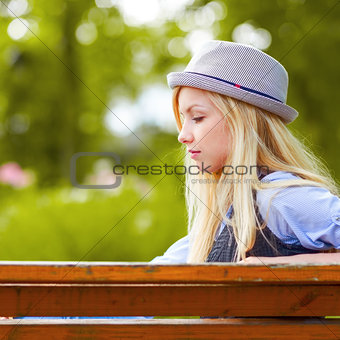 Thoughtful hipster girl sitting on bench in the park