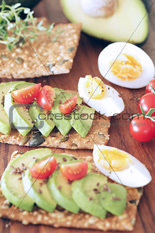 Avocado, tomato and boiled egg on pumpkin seeded crackers - shallow dof