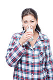 Woman in plaid pajamas drinks milk before bed on a white backgro