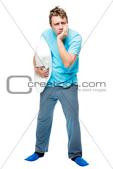 Sleepy man in pajamas with a pillow in his hand on a white backg