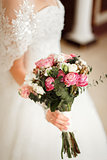 Bride holding a beautiful bouquet of rose and white flowers.