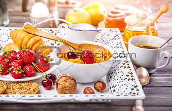 Breakfast with cornflakes berry honey and croissant