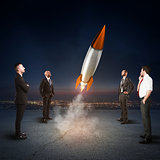 Team of businesspeople looks start a missile. Concept of company startup and new business. 3D Rendering.