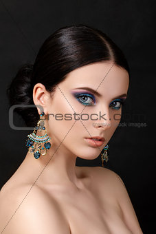 Portrait of beautiful brunet woman with blue earrings