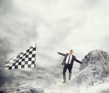 Business concept of businessman who overcome the problems reaching the flag on a rope