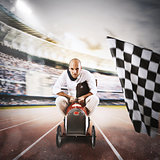Successful businessman in a small car on the finishing line