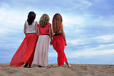 Young women in a long dress standing on the beach in summer evening.