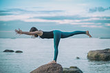 Young attractive woman practicing yoga, standing in Warrior three exercise, Virabhadrasana III pose
