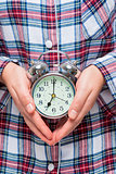 Close-up of an alarm clock in female hands on a background of pa