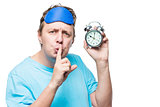 Man with an alarm clock showing a gesture quietly in a mask for
