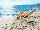 Girl tans on a deck chair on a beautiful beach