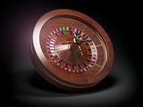 Casino roulette wheel on black background.