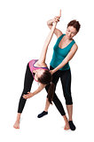 Trainer helping woman with positioning on her yoga pose.