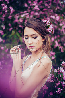 Portrait of young beautiful woman posing in spring blossom trees.