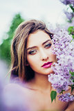 Portrait of young beautiful woman posing among lilac trees.