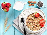 bowl with muesli, fresh strowberry, nuts, chia seeds and milk