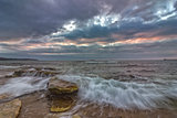 long exposure seascape with slow shutter and waves flowing out at sunset