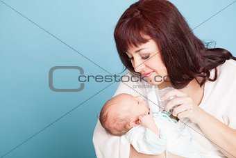 mom is feeding the baby milk from a bottle