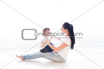 mom plays with her son on the floor of the happiness
