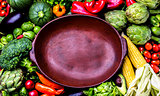 Cooking background concept. Fresh organic vegetables around empty clay pot