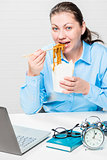Hungry girl eating noodles at the office