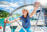 Little boy captain on board of sailing yacht on summer cruise. Travel adventure, yachting with child on family vacation.