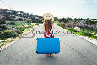Beautiful woman walking on the road in hat holding suitcase. Back view, travel concept.